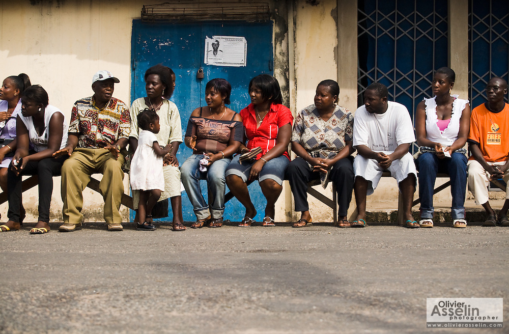 People sit on a bench in the street as they wait to vote at a polling station in Ghana's capital Accra during presidential and parliamentary elections on Sunday December 7, 2008.