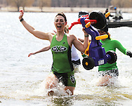 Rachel Reed, of Palo, part of the Midwest Xtreme Tri Club team, holds up a toy tricycle as she runs through the water at the Polar Plunge event at Pleasant Creek State Recreation Area in Palo on Saturday March 26, 2011. 28 team participated in the event which was sponsored by local law enforcement agencies and raised money for Special Olympics Iowa.