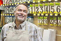 Happy mature salesperson in hardware store looking away