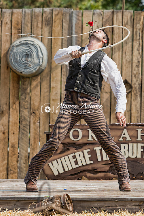 Loop Rawlins uses his whip cracking skills to remove a rose from his lips during a performance at the 2013 Oklahoma State Fair in Oklahoma City on Monday, Sept. 16, 2013.  (Photo copyright © 2013 Alonzo J. Adams)