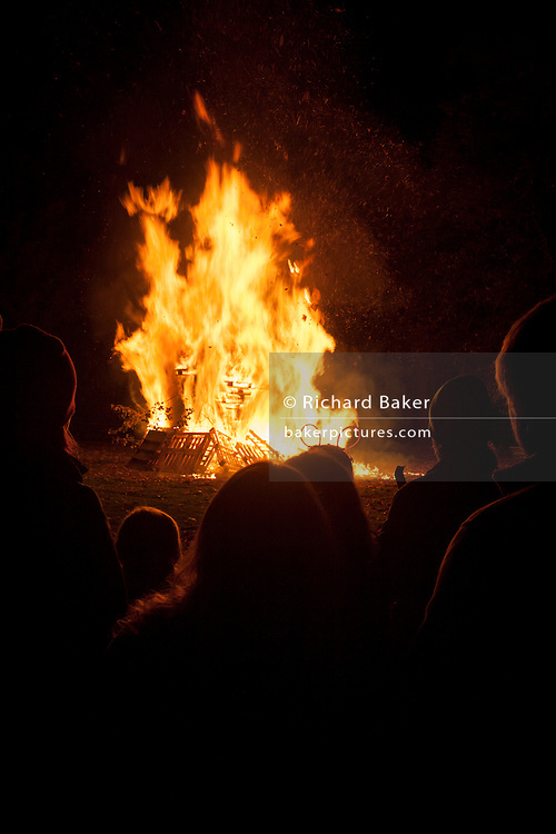 Dark figures watch the flames of a bonfire during the annual November 5th fireworks in Kington, Herefordshire, England