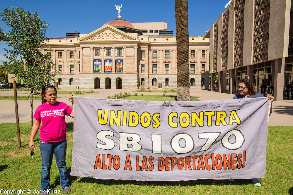25 JUNE 2012 - PHOENIX, AZ:  Immigration supporters picket the Arizona state capitol after the US Supreme Court overturned most of SB1070 Monday. The case, US v. Arizona, determined whether or not Arizona's tough anti-immigration law, popularly known as SB1070 was constitutional. The court struck down most of the law but left one section standing, the section authorizing local police agencies to check the immigration status of people they come into contact with.       PHOTO BY JACK KURTZ