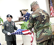 Ret. CSM Herman Trimble (right) folds the flag as Ret. CSM Wallace Pascall (left) holds the flag.  Ret. Lt. Col. Henry Moreman (middle) reads to the audience what each fold of the flag signifies.  After the flag was folded, Trimble presented the flag to Opelika mayor Gary Fuller.  Photo by Elliot Knight