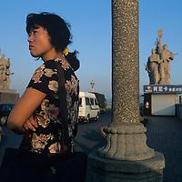 China, Jiangxi Province, Nanjing, Woman waits at bus atop Yangtze River Bridge in Nanjing at sunset.