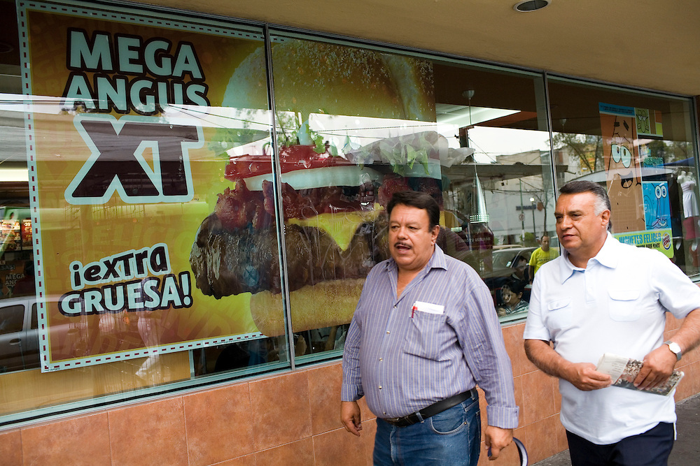 "People walk in front of a Burger King advertising an ""Extra Thick Mega Angus Burger"" in Mexico City."