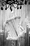 A lingerie store window display of a white lace corset hanging from a chandelier.