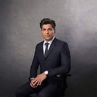 Corporate portrait 3/4 length textured grey background fully styled and colour graded featuring asian business man sat on stool