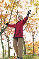 Happy Mature Caucasian woman walking with arms out as if in celebration below Fall colored trees in a park like setting.<br />