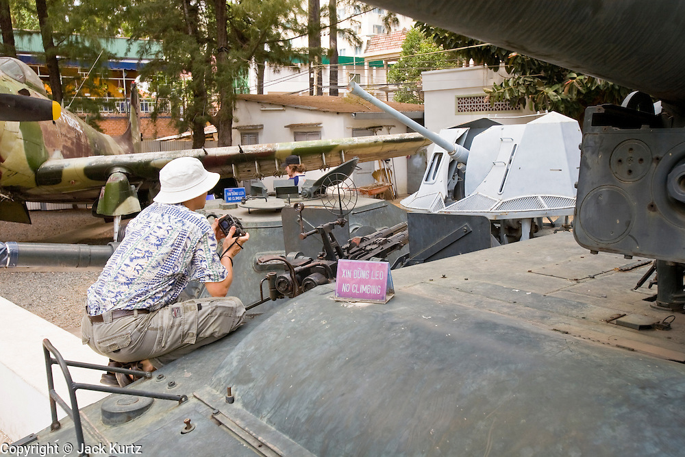 09 MARCH 2006 - HO CHI MINH CITY, VIETNAM: A tourist climbs on a captured American armored vehicle at the War Remnants Museum in Ho Chi Minh City (Saigon), the former capital of South Vietnam. The War Remnants Museum displays American weapons and material captured by North Vietnamese and Viet Cong forces during the US war in Vietnam. PHOTO BY JACK KURTZ