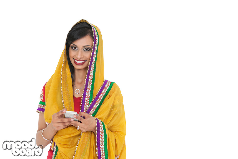 Portrait of young Indian woman in traditional wear holding cell phone against gray background
