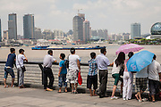 People watch Huangpu River activity along the Bund Shanghai, China