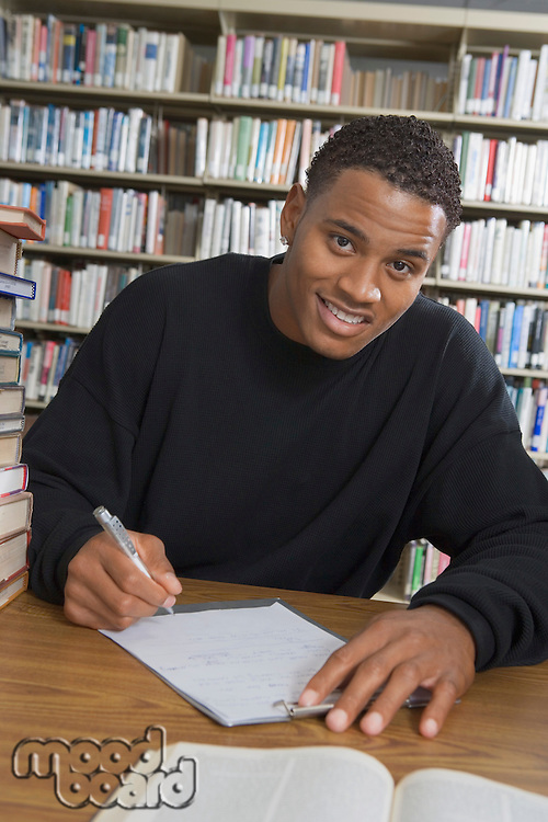 Male student making notes in college library