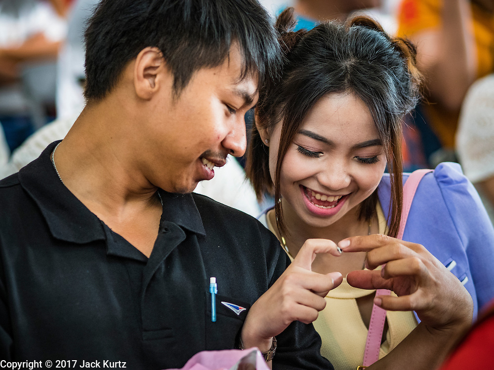 """14 FEBRUARY 2017 - BANGKOK, THAILAND:  A couple waits to get married in the Bang Rak district in Bangkok. Bang Rak is a popular neighborhood for weddings in Bangkok because it translates as """"Village of Love."""" (Bang translates as village, Rak translates as love.) Hundreds of couples get married in the district on Valentine's Day, which, despite its Catholic origins, is widely celebrated in Thailand.     PHOTO BY JACK KURTZ"""