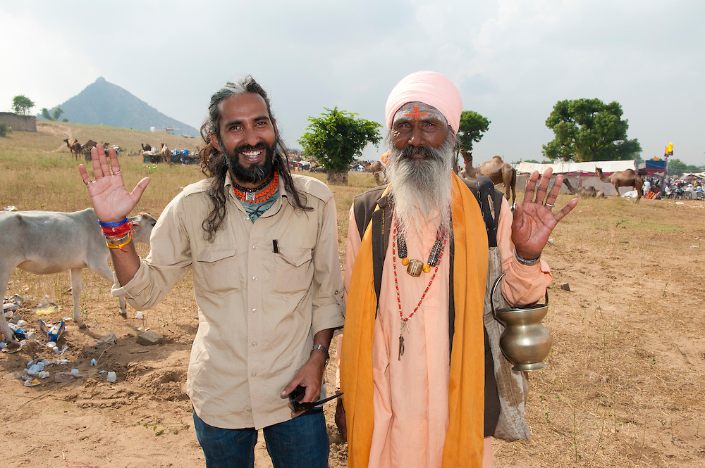 Young modern Indian man stands laughing with a Sadhu holy man at Pushkar Fair. A happy image showing the contrast of the new and more traditional India.