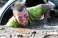 A competitor emerges from the belly crawl at the Muckfest MS Los Angeles on October 25, 2014.  Image Credit: Amanda Schwarzer