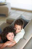 Affectionate couple sitting on couch in living room elevated view