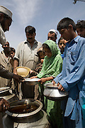 Residents from SWAT valley begin arriving at Shaik Shazad IDP camp at outside of Mardan in North West Frontier Province...Children queue for food distributed by a local NGO at Shaik Shazad IDP Camp...Within four days more than 2000 families have reportedly registered as IDP's seeking shelter and food at the hastily arranged camp. According to UNHCR Some 500,000 residents have fled SWAT and neighboring provinces since August 2008. On Thursday the Pakistan Government announced a military operation to 'eliminate' Taliban militants form the SWAT Valley. A further 1 million IDP's are expected in the coming weeks as the military advances throughout SWAT valley towards achieving their military goals..