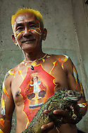 Man with his Iguana and body painting of Santo Nino the local patron saint of Cebu. Like the image's counterpart in Prague, the figure is clothed in expensive textile robes mostly donations from fervent devotees in the Philippines and abroad. The statue is the oldest Catholic relic in the Philippines and permanently housed since 1565 at the Basilica Minore del Santo Niño in Cebu City.