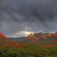 A rainbow fades in and out among the rain clouds in Sedona