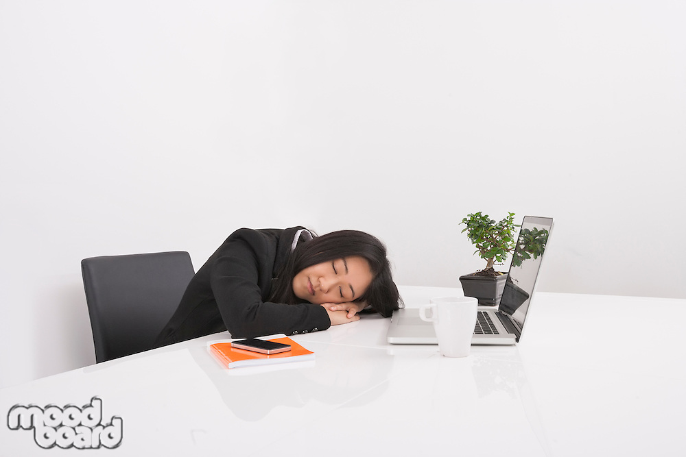 Overworked businesswoman resting at desk in office