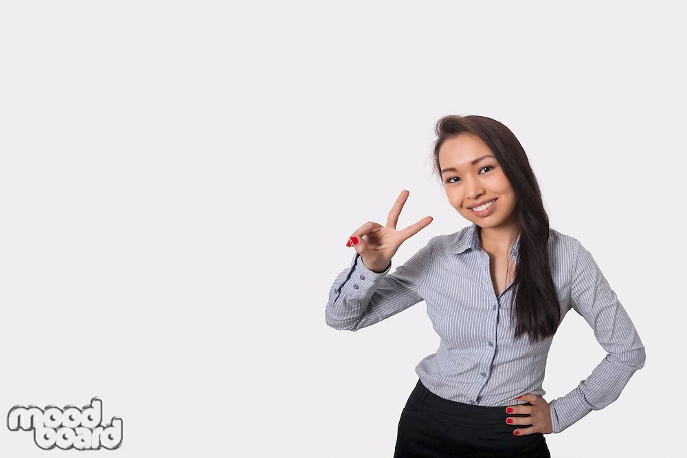 Portrait of happy businesswoman showing victory sign against gray background