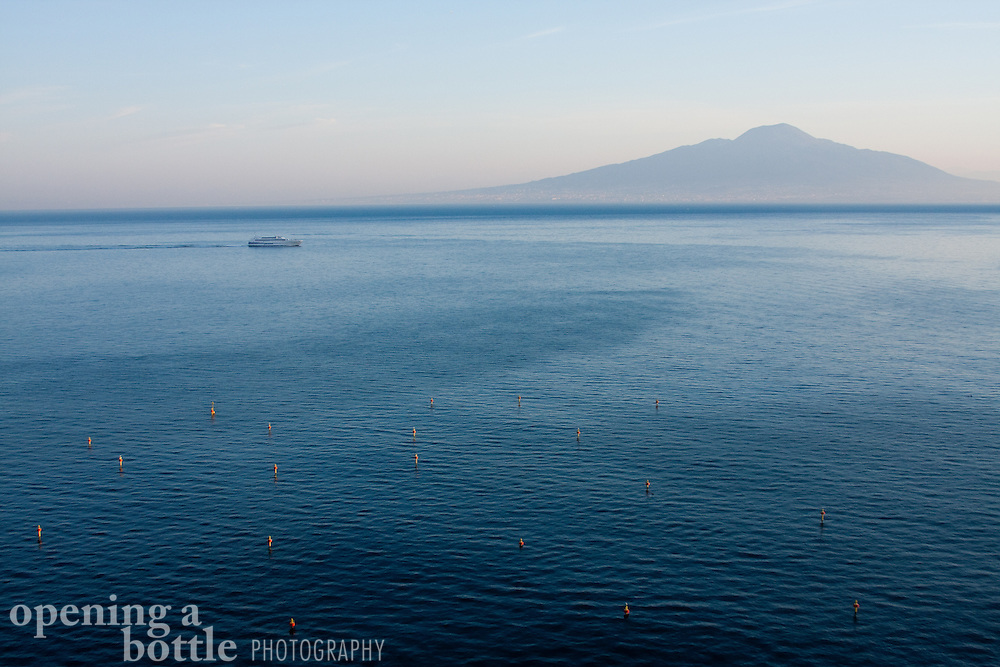 A ferry crosses the Bay of Naples en route to Sorrento from Capri, with Mt. Vesuvius in the distance, as seen from Sorrento, Campania, Italy.