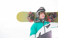 young man carrying snowboard against clear sky
