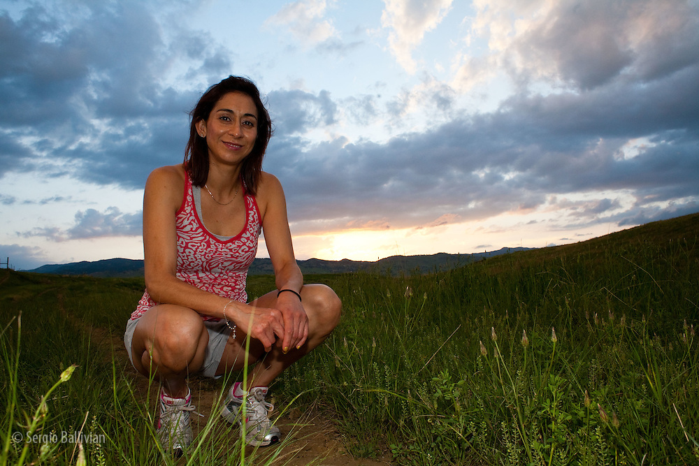 A woman ties her shoes after running on a dirt trail at dusk in Boulder, Colorado.