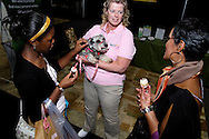 Carrie Shapiro of FirstLight Home Care holds her 3-year-old German miniature schnauzer for Mary-Lily Williamson, 11 of Dayton as she chats with Sharon Williamson of Dayton (right) during the Dayton Women's Fair at the Airport Expo.Center in Vandalia., Saturday, September 17, 2011.