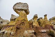 White capped hoodoos with yellow base. Paint Mines Interpretive Park is run by El Paso County, near Calhan, Colorado. Its colorful sediments outwashed from the Rockies 55 million years ago. The Paint Mines are named for their colorful clays that were collected by American Indians to make paint. Oxidized iron compounds cause brightly colored bands in various layers of clay. When outcrops erode, a hard capstone allows columns of clay to be preserved beneath, creating fantastic spires called hoodoos. Selenite (gypsum) contributes to the color, and white quartzitic crystals dazzle the eye.