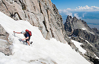 Noah Brenner traverses a snowfield high on the south face of Mount Owen (ele. 12,928) during a successful summit bid of the peak in Grand Teton National Park. Teewinot Mountain (ele. 12,325) is visible in the distance.