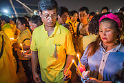 05 DECEMBER 2012 - BANGKOK, THAILAND: Thais light their candles for the candle light vigil during the public ceremony to celebrate the birthday of Bhumibol Adulyadej, the King of Thailand, on Sanam Luang, a vast public space in front of the Grand Palace in Bangkok Wednesday night. The King celebrated his 85th birthday Wednesday and hundreds of thousands of Thais attended the day long celebration around the Grand Palace and the Royal Plaza, north of the Palace. The Thai monarch is revered by most Thais as unifying force in Thailand's society, which is not yet recovered from the political violence of 2010.      PHOTO BY JACK KURTZ