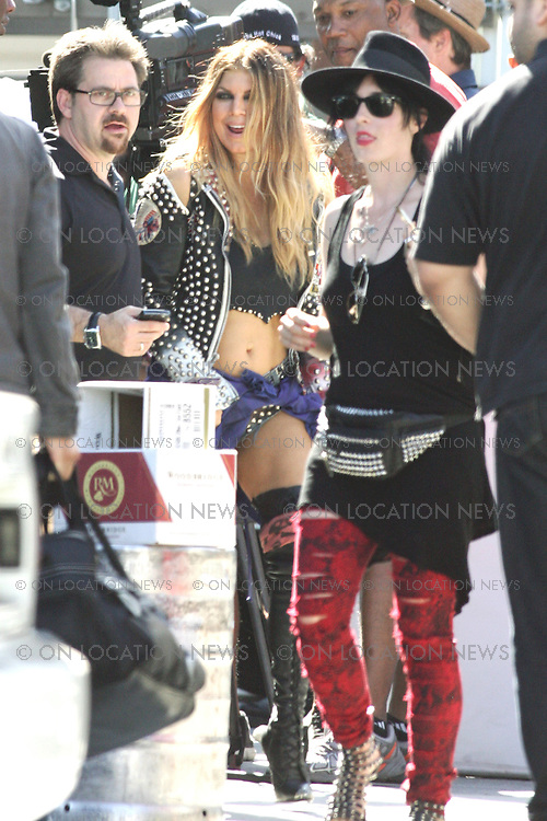 "August 27th, 2010  Hollywood CA, ***EXCLUSIVE*** Fergie and Slash film a music video together for ""Beautiful Dangerous"" before performing together live at the third annual Sunset Strip Music Festival in Hollywood. Fergie and Slash filmed scenes for the video at the famous Jumbo's Clown Room burlesque strip bar where a blond  haired Fergie performed as a stripper with Slash in the audience. Another scene took place at a cheap hotel nearby. In that scene Slash was tied to a bed and at the mercy of Fergie the stripper! On the wall of the hotel room was seen all kinds of Slash memorabilia from over the years suggesting that Fergie was obsessed with Slash. Photo by Danny Mayer/Eric Ford/ On Location News 818-613-3955 info@onlocationnews.com"