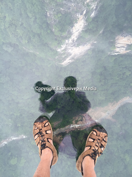 ZHANGJIAJIE, CHINA - JUNE 25:<br /> <br /> A visitor takes photos of his foot on glass-bottomed bridge during the safety test at Zhangjiajie Grand Canyon on June 25, 2016 in Zhangjiajie, Hunan Province of China. World\'s tallest and longest glass-bottomed bridge has been completed and took a global broadcast through television and internet medias to show its safety. More than thirty citizens and visitors thumped the bridge with hammer in the test event. <br /> ©Exclusivepix Media
