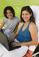 Mother and Son Using Laptop Outside