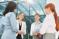 Smiling businesswomen conversing in office