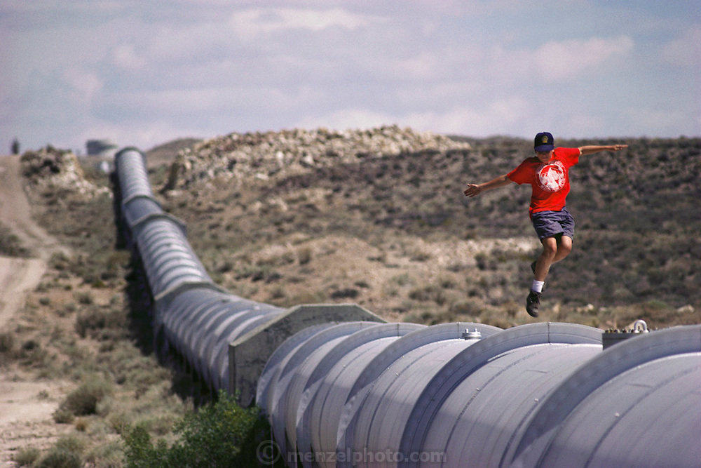 Alex Wright, 14, skips along the top of a pipe that is part of the California Aqueduct water transport system. Owens Valley, east of the Sierra Nevada mountains, along Route 395. Los Angeles Aqueduct. MODEL RELEASED.