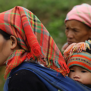 A young mother and her child at the Lung Khau Nhin Market. Vietnam. Lung Khau Nhin Market is rural tribal market hiding itself amongst the mountains and forests of the far north Vietnam about 10 km from the border with China. The market plays an important role for the local ethnic people, Flower Hmong, Black Zao, Zay, and very small ethnic groups  Pa Zi, Tou Zi, Tou Lao. Tourist trips to the market run from Sapa and Lao Cai every week. Lung Khau Nhin Market, Vietnam.15th March 2012. Photo Tim Clayton