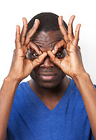 Portrait of playful young man with hands over eyes against white background