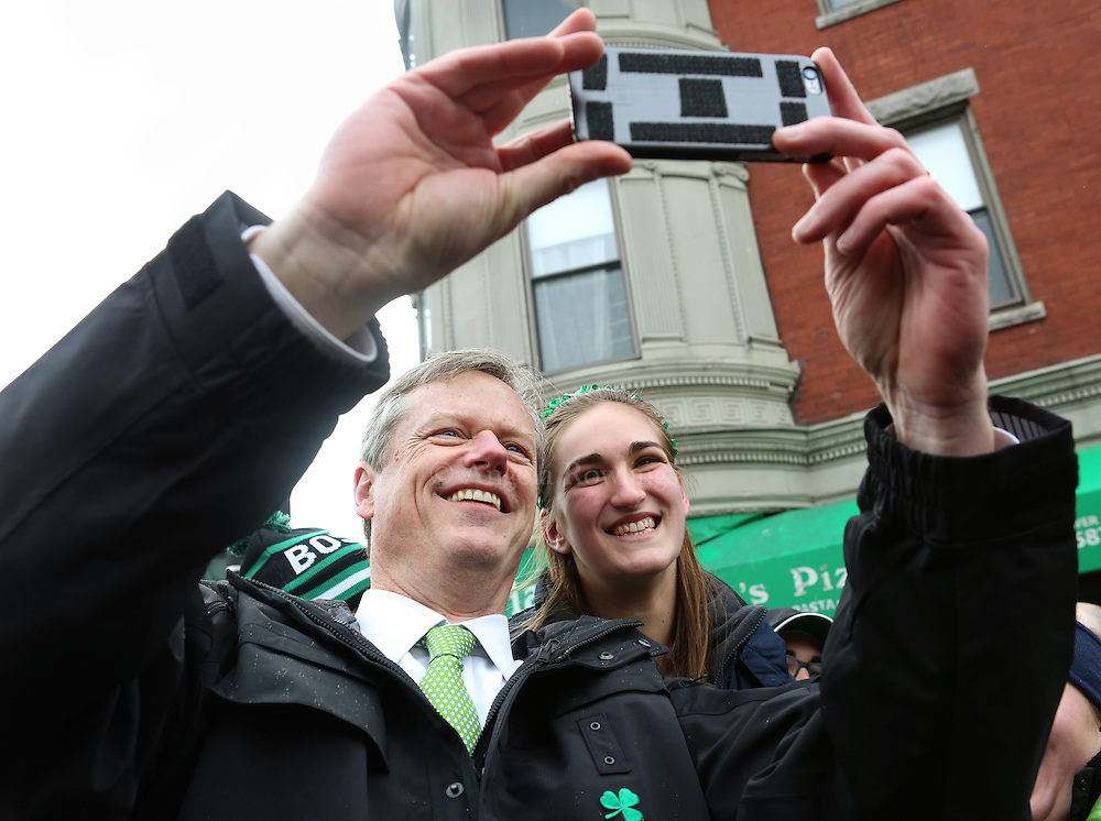 (Boston, MA - 3/15/15) Gov. Charlie Baker takes a selfie with a young woman during the St. Patrick's Day Parade in South Boston, Sunday, March 15, 2015. Staff photo by Angela Rowlings.