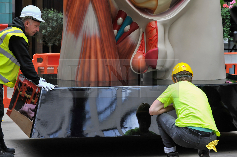 """© Licensed to London News Pictures. 24/06/2017. London, UK. Workmen install a 21 feet tall, 2.5 tonne bronze sculpture called """"Temple"""" by Damien Hirst near the Lloyds Building in the City of London.  The artwork will be on display as part of """"Sculpture in the City"""", a festival of sculpture in the City of London showing works by leading artists. Photo credit : Stephen Chung/LNP"""