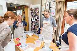 Baker Liz Wilson leads a class with participants Hazel Griffiths, left, Jess Hayden, second right and Susie Mullen learn a number of baking methods at her Fulham home in London. London, August 16 2019.