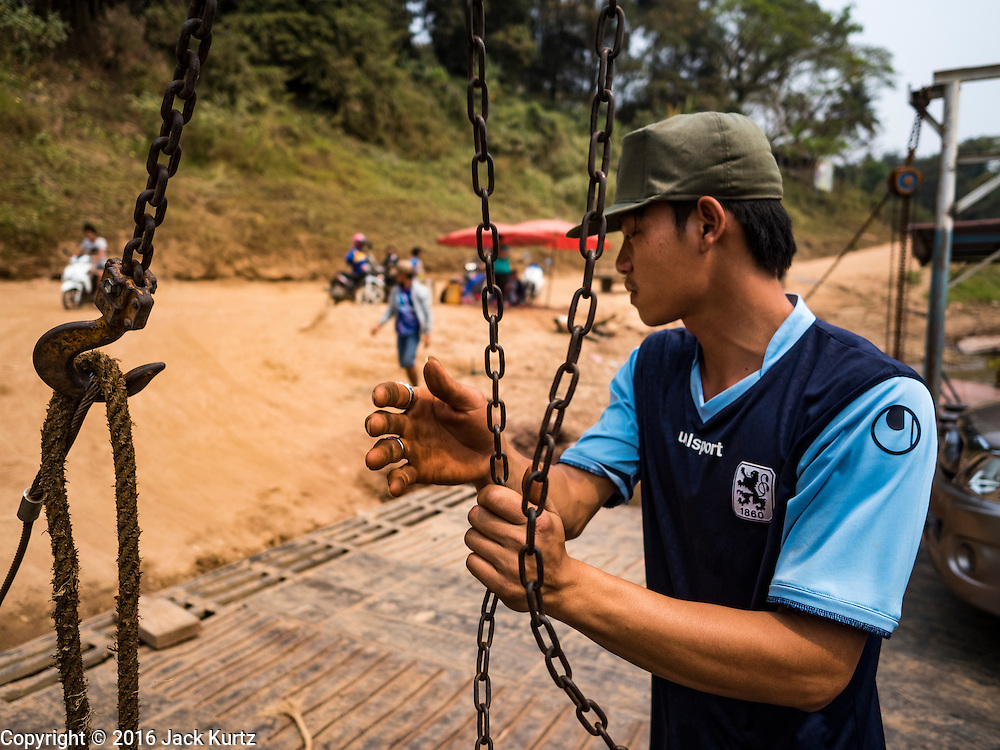 11 MARCH 2016 - LUANG PRABANG, LAOS:  A crewman lowers the ramp on a ferry across the Mekong River near Luang Prabang. Laos is one of the poorest countries in Southeast Asia. Tourism and hydroelectric dams along the rivers that run through the country are driving the legal economy.      PHOTO BY JACK KURTZ