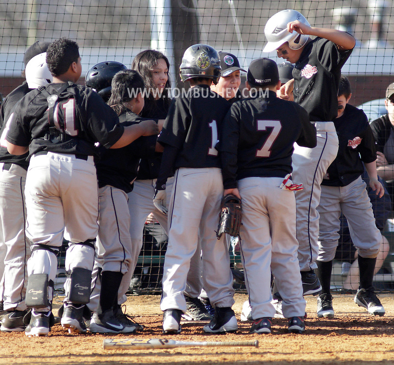 Chester, New York  - A player, at right, from the Jersey City Dawgs jumps onto home plate after hitting a home run as his teammates gather to congratulate him during the TRUMP March Madness youth baseball tournament at The Rock Sports Park on March 18, 2012. ©Tom Bushey / The Image Works