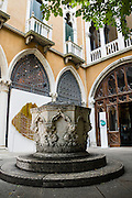 """Old well, at Istituto Veneto di Scienze Lettere ed Arti (Palazzo Cavalli Franchetti), Venice, Italy, Europe. Because Venice was cut off from reliable sources of fresh water, Venetians built underground clay-lined cisterns to collect and filter rainwater. Many wellheads were decorated with carvings of saints, family crests, inscriptions in Carolingian, Byzantine, Gothic, Renaissance, and Baroque era styles. An aqueduct from the mainland completed in the late 1800s made these wells obsolete. Venezia is the capital of Italy's Veneto region, named for the ancient Veneti people from the 900s BC. The romantic """"City of Canals"""" stretches across 117 small islands in the marshy Venetian Lagoon along the Adriatic Sea in northeast Italy, between the mouths of the Po (south) and Piave (north) Rivers. The Republic of Venice was a major maritime power during the Middle Ages and Renaissance, a staging area for the Crusades, and a major center of art and commerce (silk, grain and spice trade) from the 1200s to 1600s. The wealthy legacy of Venice stands today in a rich architecture combining Gothic, Byzantine, and Arab styles."""