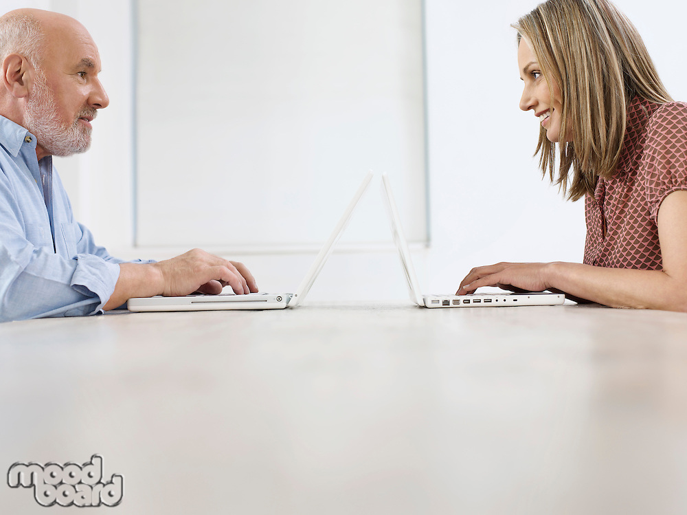 Middle-aged man and mid-adult woman sitting opposite to each other using laptops profile