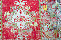 An antique rug is worn down to the warp in spots, but the colors are still vibrant. Woodlawn Museum, Ellsworth, Maine.