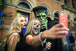 © Licensed to London News Pictures . 31/10/2015 . Manchester , UK . Women pose for a selfie with Frankenstein's monster . Halloween revellers , wearing make up and costumes , out and about in Manchester City Centre . Photo credit : Joel Goodman/LNP