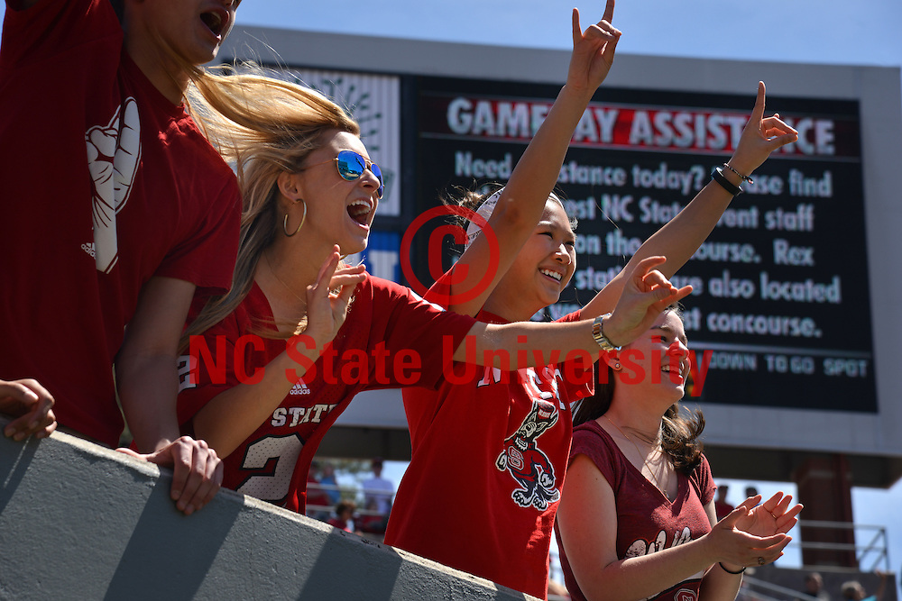 Students cheer on the Wolfpack as they take the field for a football game.