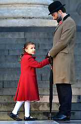 © Licensed to London News Pictures. 11/11/2012. City of London, UK A young girl wearing a poppy red coat waits with her father. People arrive at a service of remembrance to remember those killed in action during conflict at St Pauls Cathedral, today 11 November 2012. Both Armistice Day and Remembrance Sunday fall of the same day this year. Photo credit : Stephen Simpson/LNP